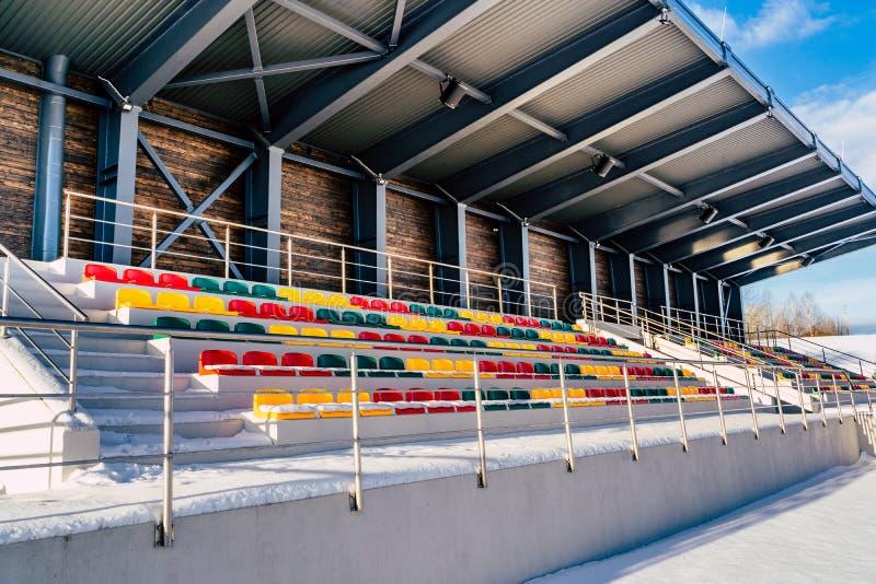 空的五颜六色的橄榄球(;Soccer);体育场位子在雪包括的冬天-晴朗的冬日 库存图片