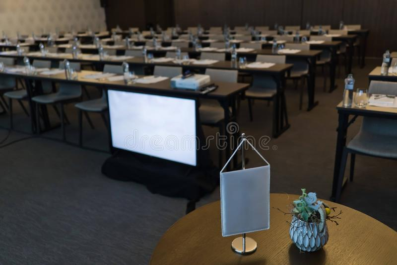空的会议室、白旗在前景,显示器、椅子和桌 库存图片