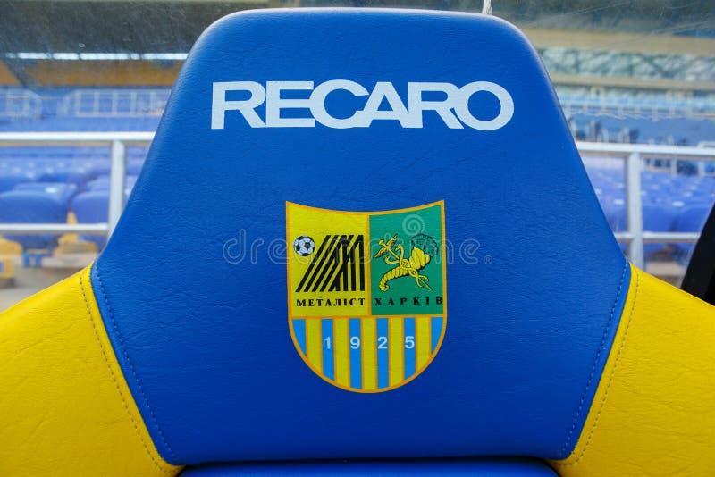 空的体育场& x22; Metalist& x22; 替补前座统排椅的Recaro垫头之物与FC Metalist商标的 免版税库存照片