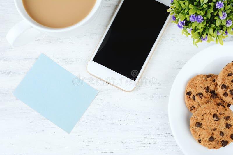 空的便条纸用咖啡、曲奇饼和手机 库存照片