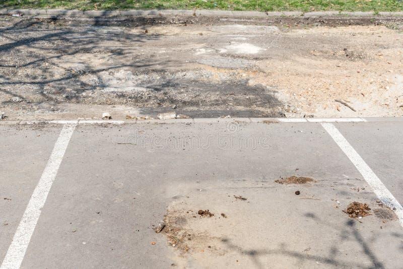 空的停车场或空间与损坏的柏油路有被剥皮的柏油碎石地面的整修和赔偿的 库存图片