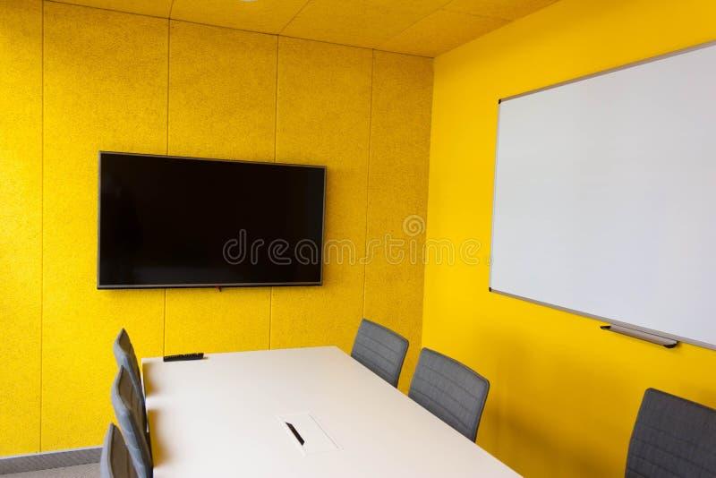 空的办公室inyellow墙壁、一张桌和灰色椅子与 免版税库存图片