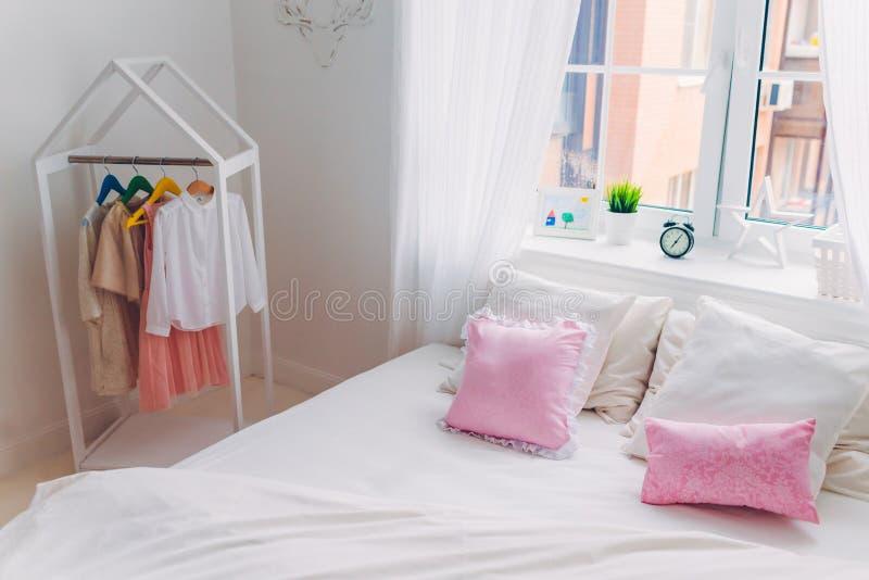 空的卧室射击没有人、桃红色枕头、大窗口、闹钟和手工制造图片的 舒适内部 免版税库存照片