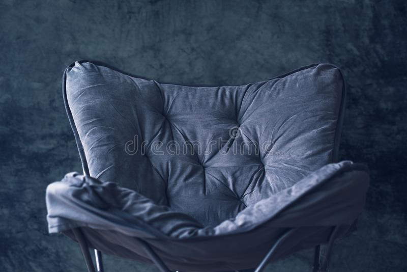 空的可折叠的椅子对灰色墙壁 免版税库存图片