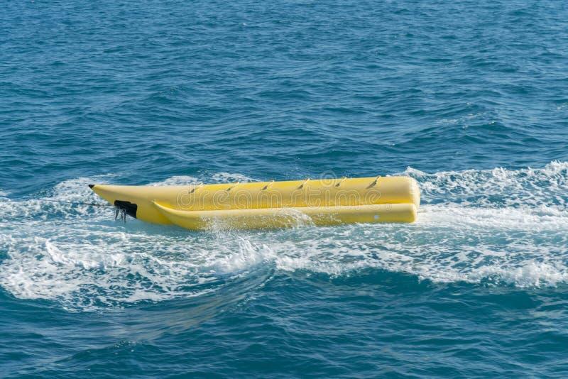 空的可膨胀的黄色香蕉船在海 乐趣的香蕉船水表面上在夏日-在海的香蕉船 库存图片