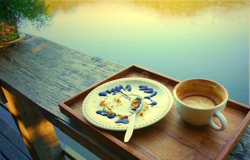 空的咖啡杯和白色板材有被吃的蛋糕碎屑的和 库存图片