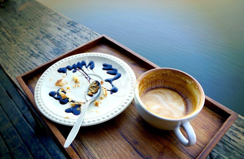空的咖啡杯和白色板材有被吃的蛋糕碎屑的和 库存照片