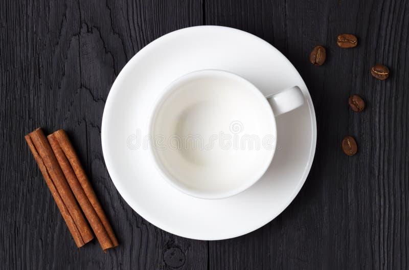 空的咖啡杯用在黑背景的一根肉桂条 免版税图库摄影