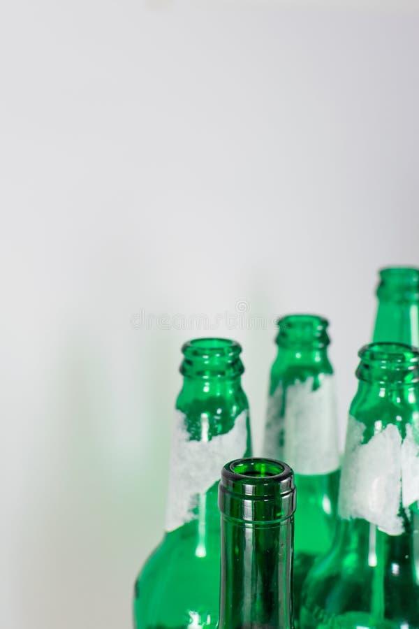 空的啤酒和酒绿色玻璃瓶瓶颈的图象在白色背景的 再用,acoholism,回收和 库存照片