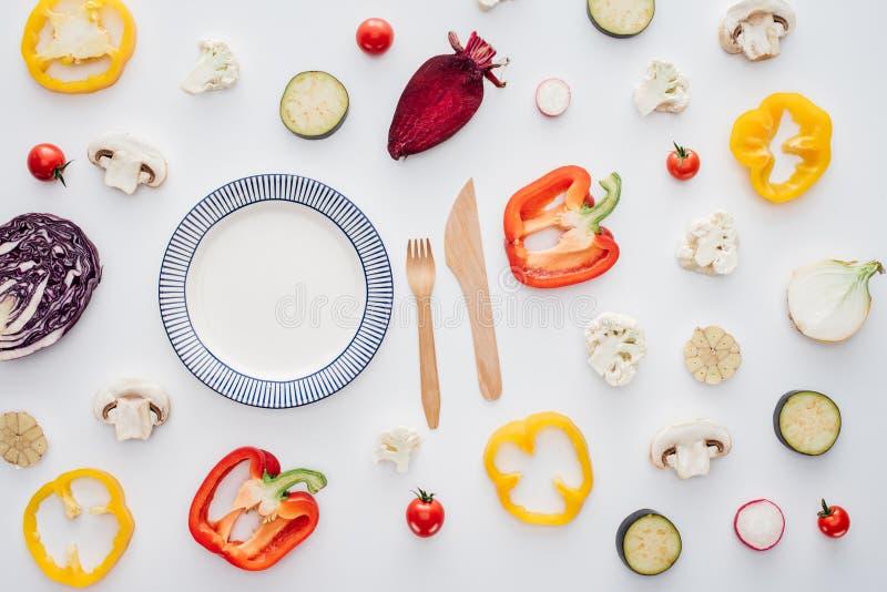 空的圆的板材、木叉子与刀子和新鲜的被切的菜顶视图  免版税库存图片
