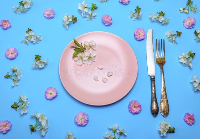 空的圆的桃红色陶瓷板材和葡萄酒刀子有叉子的 库存照片