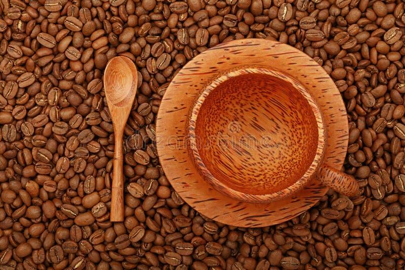 空的在咖啡豆的咖啡棕榈木杯子 库存照片