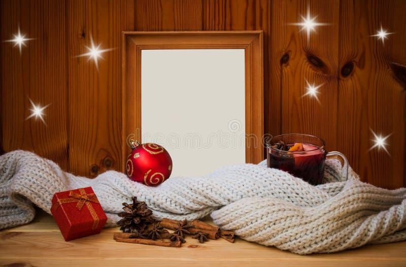 空的在围巾包裹的木制框架、杯加香料的热葡萄酒,圣诞节球、礼物和香料 库存图片