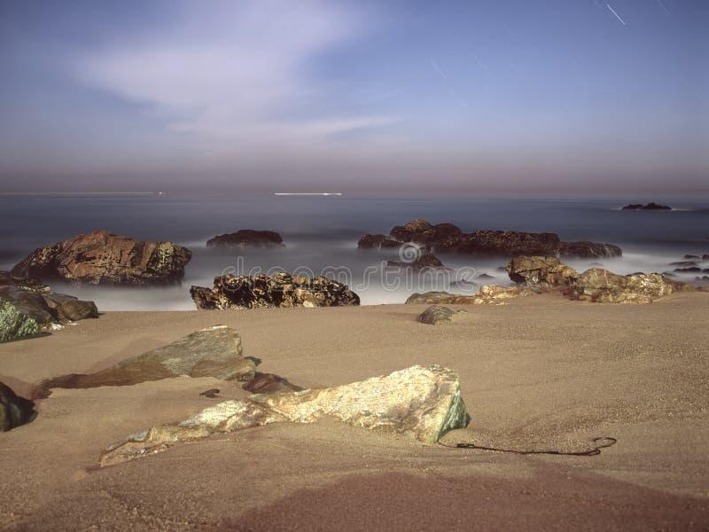 空的多岩石的海滩在晚上 免版税库存照片