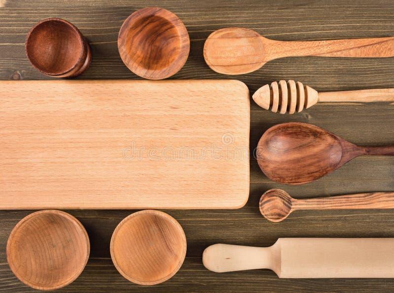 空的委员会和其他厨房器物在木背景 库存照片