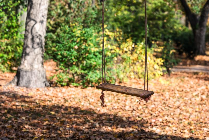 空的孩子在秋天公园系住摇摆 免版税库存图片