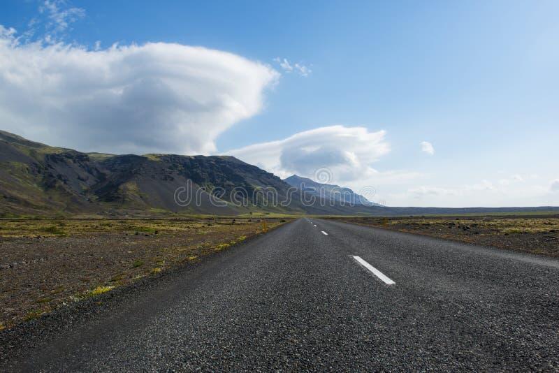 空的山和双突透镜的云彩围拢的沥青冰岛路 库存照片