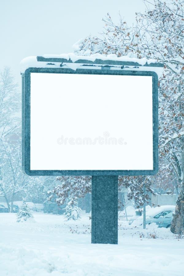 空的广告牌海报广告嘲笑在多雪的街道上 免版税库存图片