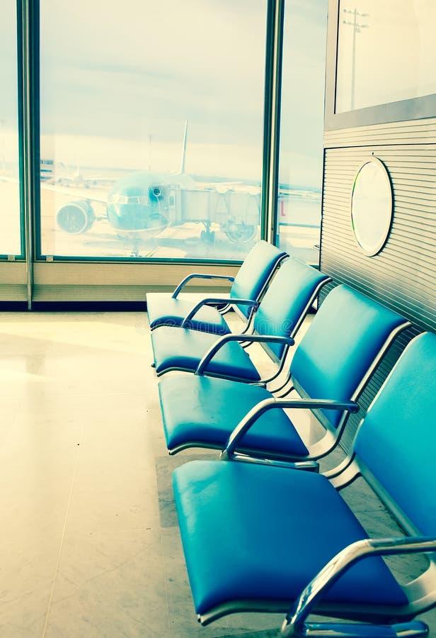 空的扶手椅子在机场和飞机的期望大厅里在窗口后 免版税库存照片
