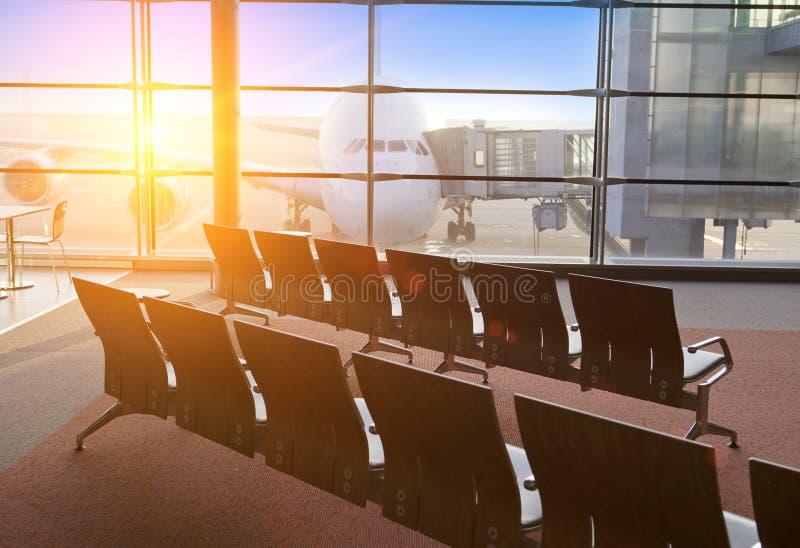空的扶手椅子在机场和飞机的期望大厅里在窗口后 库存照片