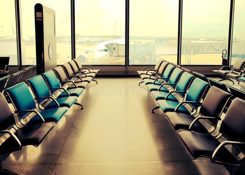 空的扶手椅子在机场大厅里,有一个减速火箭的作用的 库存图片
