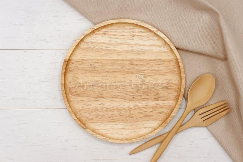 空的有匙子、叉子和米黄桌布的回合木板材在白色木桌上 免版税库存照片