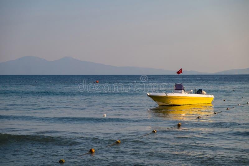 空的有土耳其的旗子的抢救黄色小船向岩石海岸的背景的海在天空蔚蓝下的 免版税库存图片