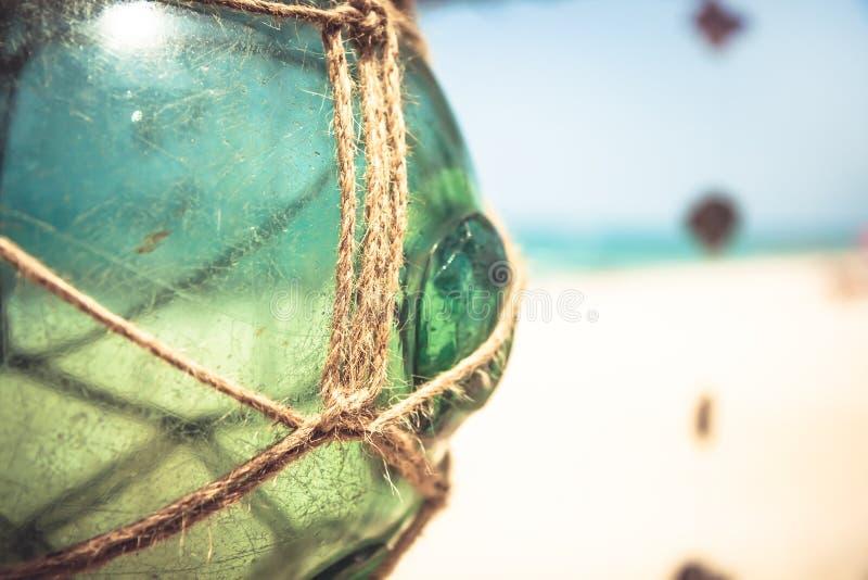 空的有绳索的葡萄酒玻璃瓶子在与被弄脏的背景和拷贝空间的热带海滩 免版税库存照片