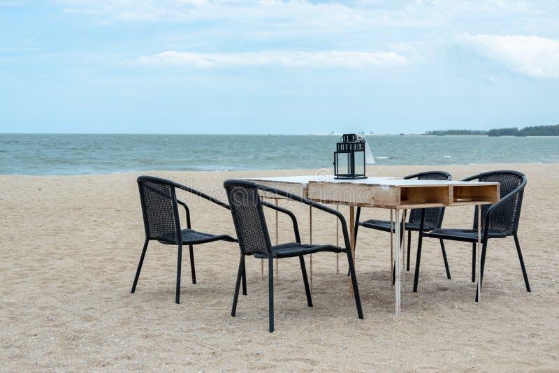 空的木桌和椅子在海滩家庭晚餐的与蓝色海 库存图片