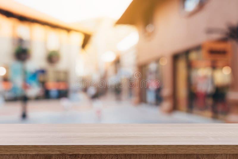 空的木桌和葡萄酒口气被弄脏defocused人群人在走的街道节日和购物中心 免版税库存照片