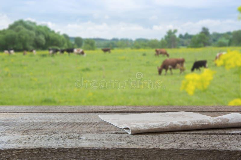 空的木桌面和母牛被弄脏的农村背景在绿色领域的 您的产品的显示 免版税库存图片
