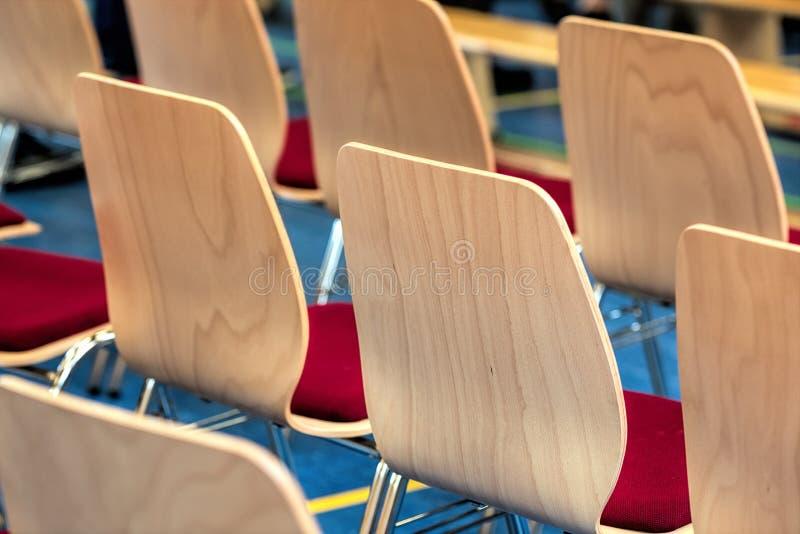 空的木椅子被弄脏的行在一个大礼堂里 空的椅子在会场里 内部会议室 库存照片