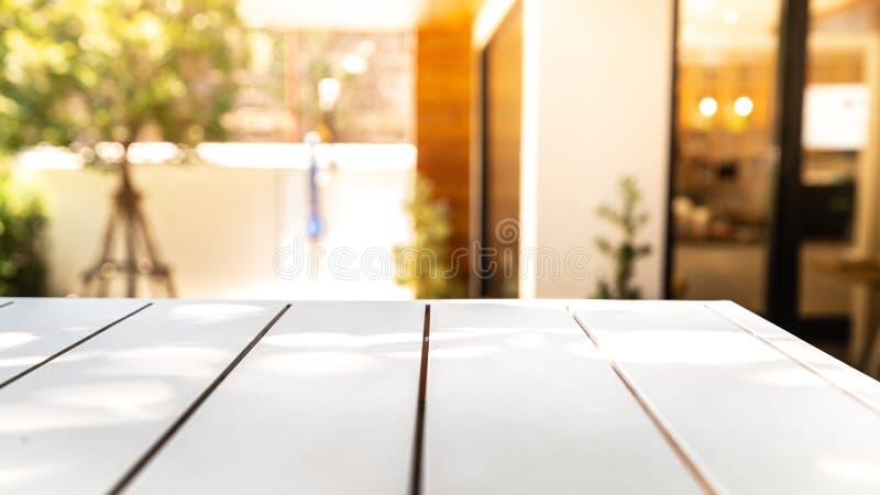 空的木白色桌和被弄脏的咖啡馆或餐馆光后面 免版税库存照片