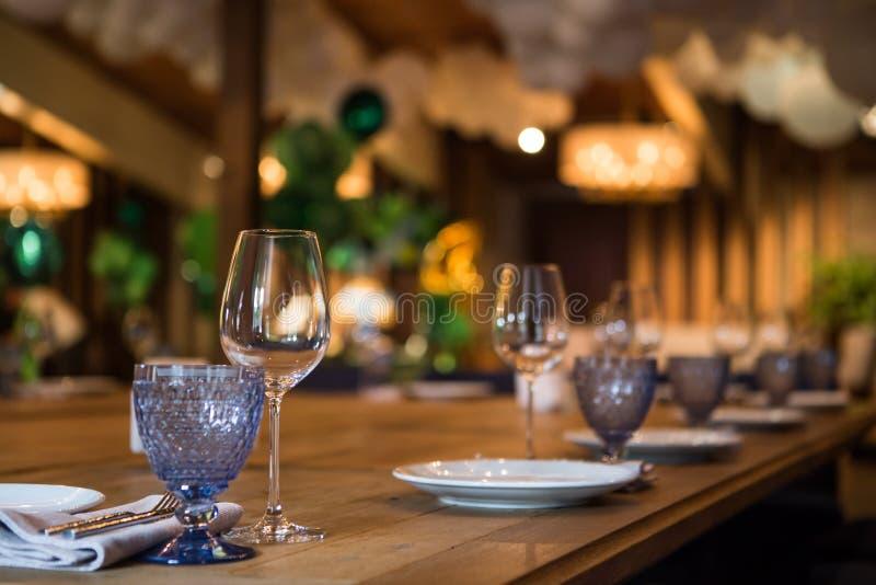 空的杯酒在一张木桌上站立 美妙地被密封的桌 免版税库存照片