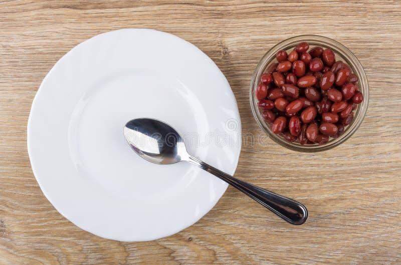 空的板材、匙子和碗用红豆在桌上 免版税库存图片