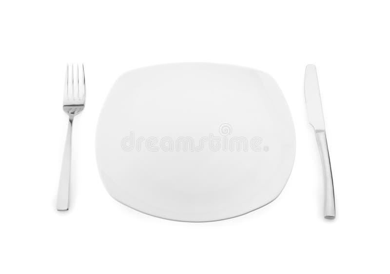 空的板材、叉子和刀子在白色背景 免版税图库摄影