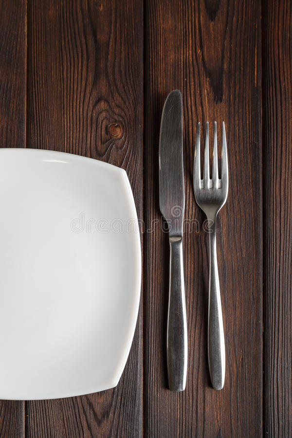 空的板材、叉子和刀子在黑暗的木背景 免版税库存照片