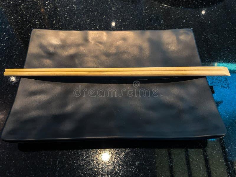 空的板材和筷子在黑织地不很细桌 库存图片