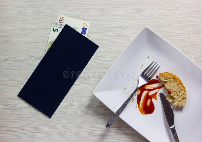 空的板材在晚餐与票据和欧洲笔记以后离开在木 库存照片