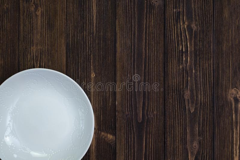 空的板材或白色盘在木桌背景,顶视图, 免版税库存图片