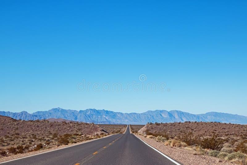 空的柏油路通过沙漠在与山的一好日子 免版税图库摄影