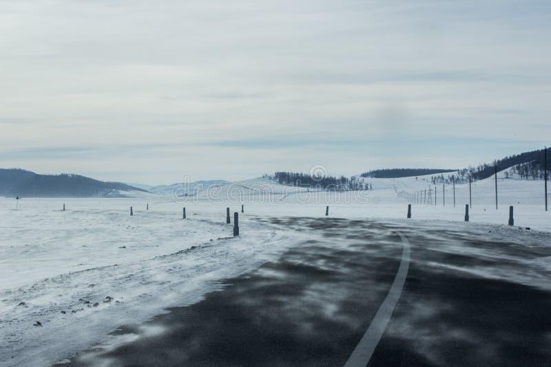 空的柏油路风景通过雪原和小山向左转 库存照片