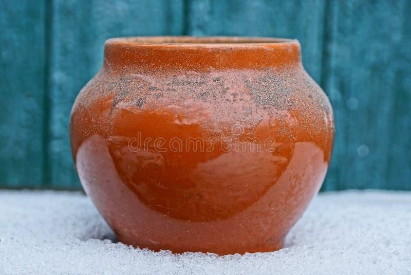 空的棕色老和肮脏的陶瓷罐在绿色背景的白雪站立 免版税库存图片