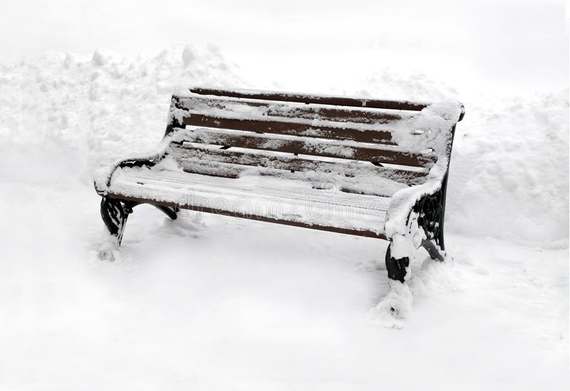 空的棕色长木凳室外在干净的白色雪在阴暗冬日 库存照片
