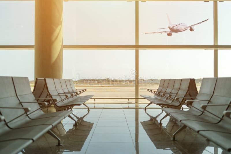 空的椅子在离开大厅里在离开在日落的飞机背景的机场 汽车城市概念都伯林映射小的旅行 免版税库存照片