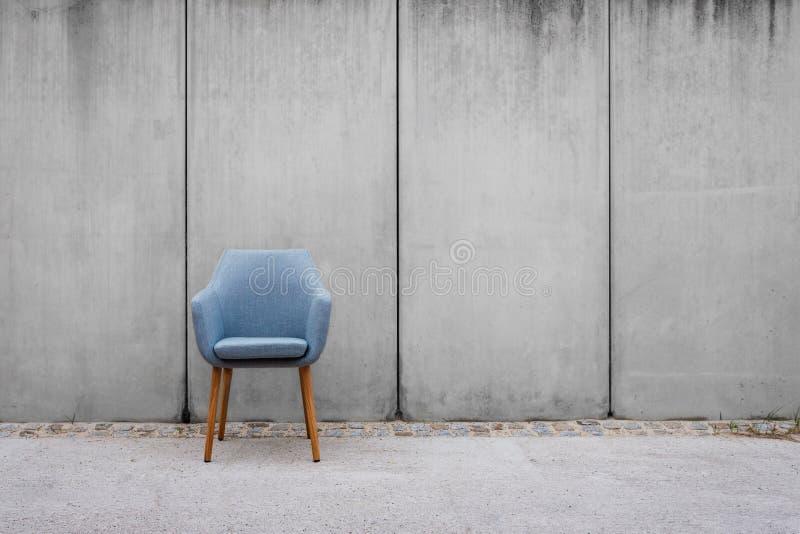 空的椅子有在边路的混凝土墙背景 库存图片