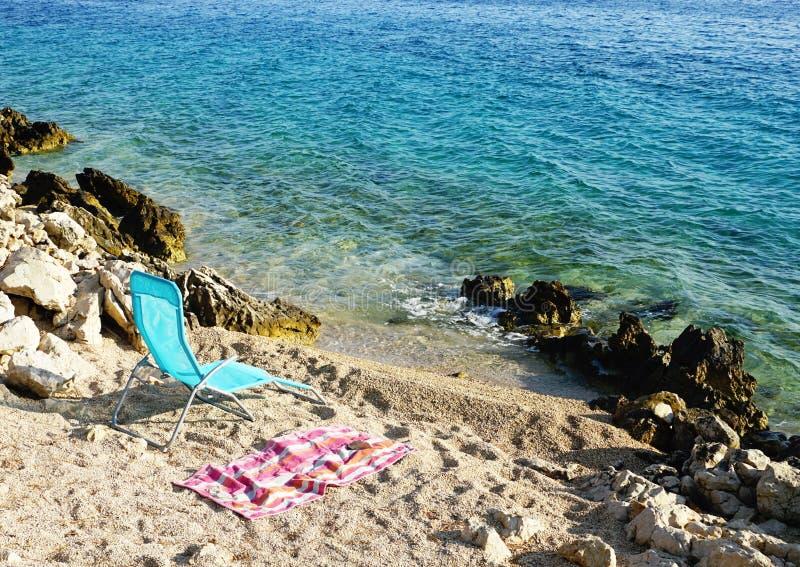空的海滩轻便折叠躺椅和海滩毛巾由沿海和海有小波浪的 免版税库存照片