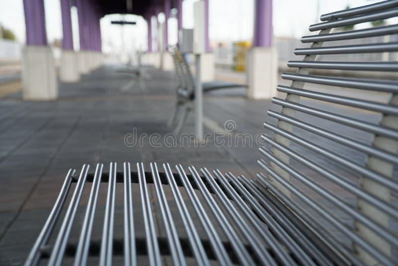 空的火车站、铁椅子或者长凳在空的平台 免版税库存照片
