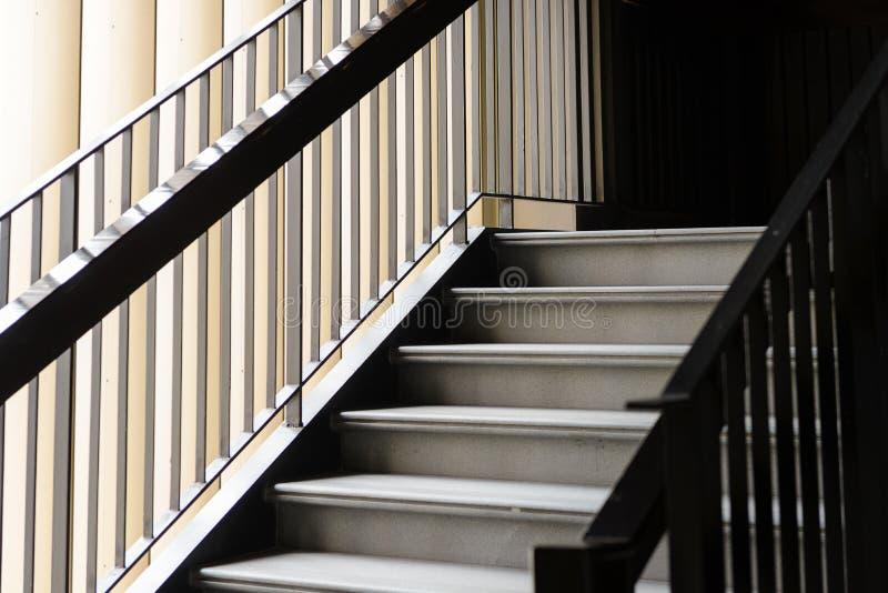 空的现代具体楼梯和黑钢扶手栏杆与自然光,楼梯在现代大厦 免版税库存照片