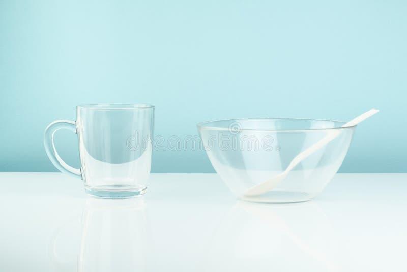 空的玻璃碗和杯子在桌上 饥饿或饮食概念:cle 库存照片